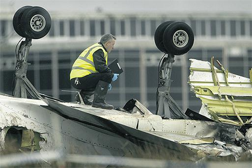 An air accident investigator stands on top of the twisted remains of the crashed Metroliner aircraft at Cork Airport yesterday