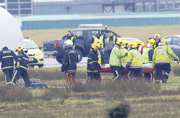 Rescue workers remove the body of one of the six people who died yesterday morning