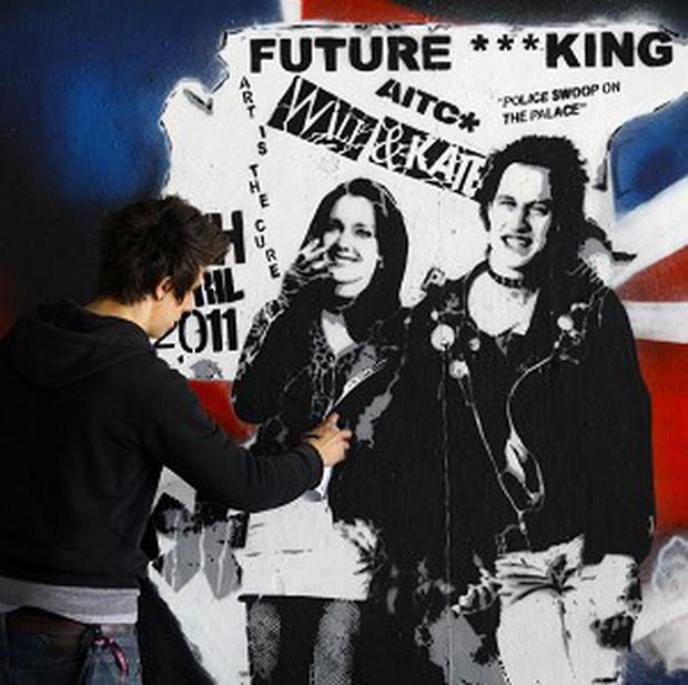 Street artist Rich Simmons puts the final touches to a mural created on the Southbank, London, in support of the upcoming royal wedding