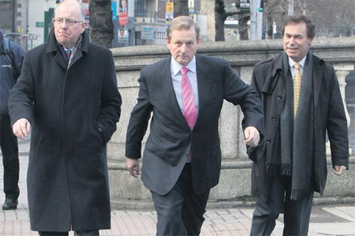 Fine Gael leader Enda Kenny strides out yesterday with the party's justice spokesman Alan Shatter (right) and spokesman on children Charlie Flanagan (left) following a press briefing on political reform at The Clarence Hotel, Dublin