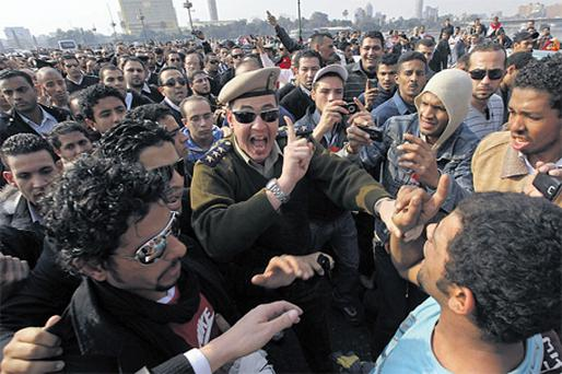 An Egyptian police officer confronts anti-Mubarak protesters in Cairo's Tahrir Square yesterday