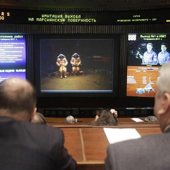 Russian space officials watch video footage of researchers simulating a landing on Mars (AP)