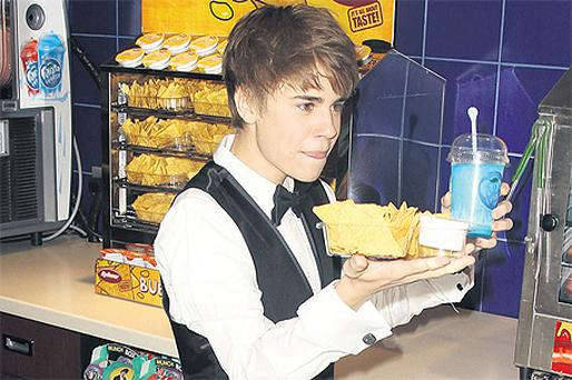 Justin Bieber helps himself to nachos and a drink at the UK premiere of 'Justin Bieber: Never Say Never' at the O2 Arena in London