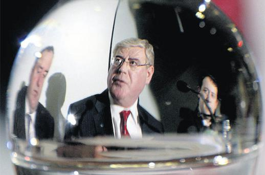 Labour leader Eamon Gilmore is seen through a glass alongside IFA president John Bryan and Labour spokesman on agriculture Sean Sherlock at the IFA headquarters in Dublin yesterday. Photo: Steve Humphreys