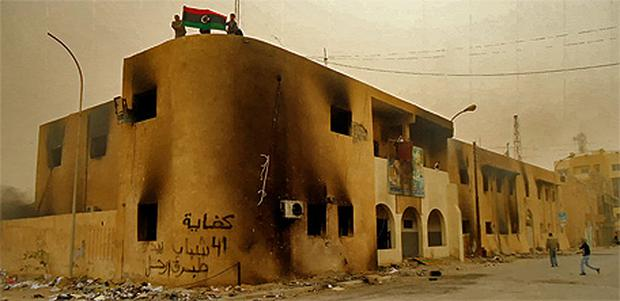 Libyan protesters hold a flag on top of a building during a demonstration in the seaport city of Tobruk. Photo: Reuters