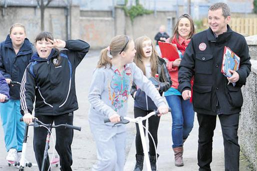 People Before Profit candidate Richard Boyd Barrett speaking to local children yesterday as he charges through housing estates in Dun Laoghaire, Dublin, to canvass for votes