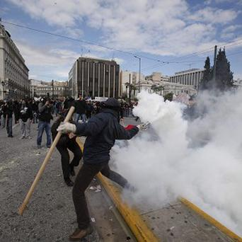 A protester throws a tear gas canister at riot police during clashes in Athens (AP)