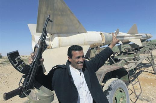 A Libyan rebel holds his AK-47 as he flashes a V sign in front an anti-aircraft missile at an abandoned military base in the east of the country