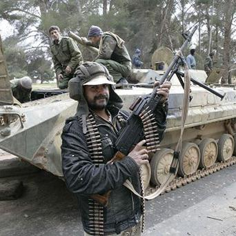 A man holding an automatic machine gun poses in front of a tank in the east Libyan city of Albayda (AP)