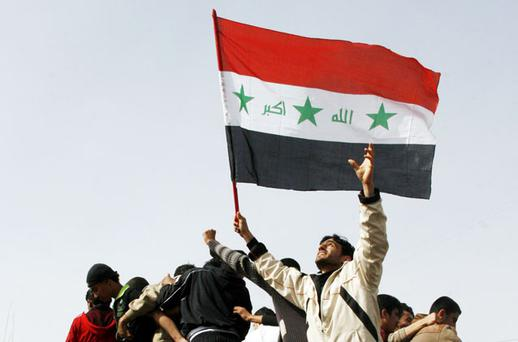 Protesters carrying the Iraqi flag climb on a military vehicle during a demonstration in Mosul. Photo: Reuters