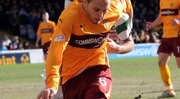Motherwell's Tom Hateley holds off the challenge of Celtic's Joe Ledley at Fir Park yesterday. Photo: PA