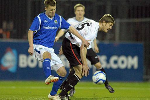 Peter Thompson (left) and Shane Guthrie battle it out at Oriel Park