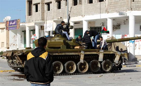 Boys climb onto the tank of Libyan army defectors in the centre of the city of Zawiyah, 50 km west of the capital Tripoli. Photo: Reuters