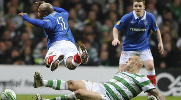Celtic's Daniel Majstovic challenges El Hadji Diouf of Rangers during their Scottish Cup clash at Parkhead last night. Photo: Reuters
