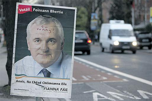 A poster of Bertie Ahern with 'sorry' scrawled on his forehead, hanging on a Dublin lamppost