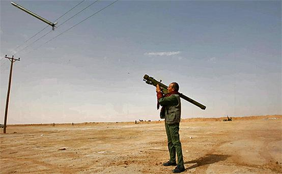A rebel fires a rocket at a Libyan air force jet loyal to leader Muammar Gaddafi during a battle in the desert near Brega. Photo: Reuters