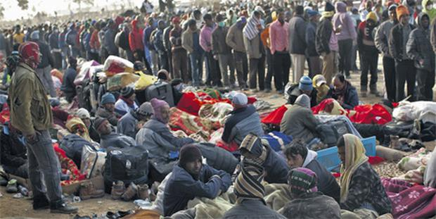 Workers from Libya who recently fled the unrest lie down, as others line up during food distribution at the Tunisia-Libyan border, in Ras Ajdir, Tunisia