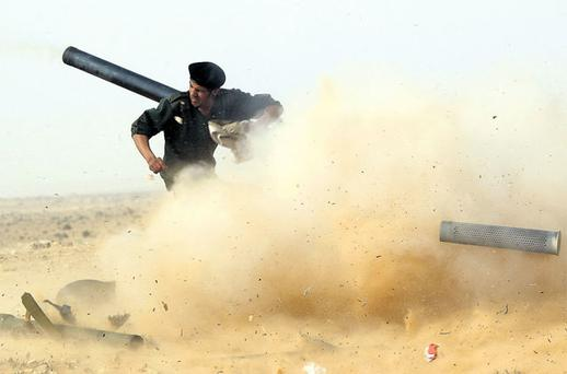 A rebel fighter fires a cannon during a battle near Ras Lanuf in Libya, yesterday. Photo: GORAN TOMASEVIC