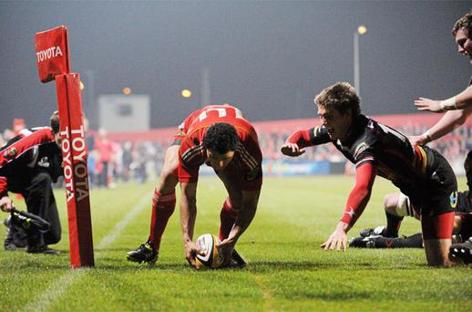 Doug Howlett, Munster, scores his side's first try despite the efforts of Matthew Pewtener, Dragons