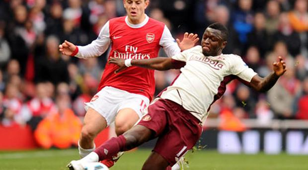 Arsenal's Jack Wilshere is challenged by Sunderland's Sulley Muntari. Photo: Getty Images