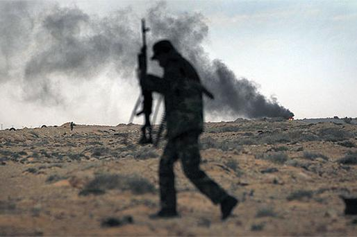 A rebel soldier pushes towards the frontline as a truck burns after being destroyed by Libyan government soldiers yesterday