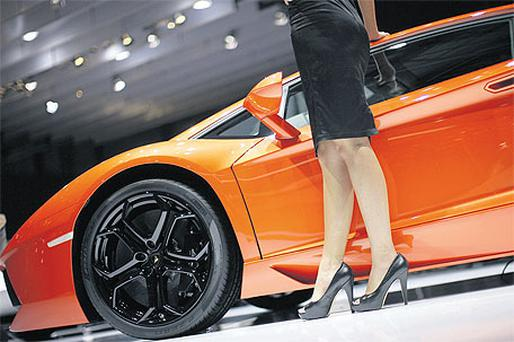 A model poses beside a Lamborghini at the Geneva International Motor Show in Switzerland earlier this month