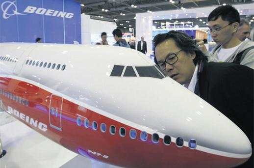 A Chinese visitor takes a close look at a model of the latest Boeing 747-8 passenger plane at the Asian Aerospace Show in Hong Kong