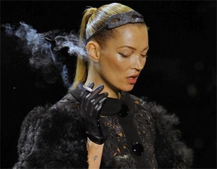 Supermodel Kate Moss smokes a cigarette during the Louis Vuitton show in Paris yesterday