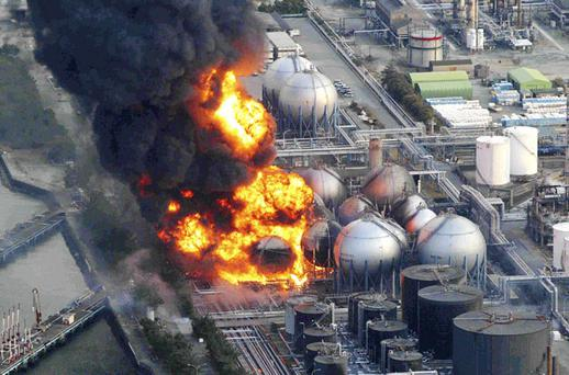 Natural gas storage tanks burn at the Cosmo oil refinery in Ichihara city. Photo: Reuters