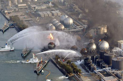 DESPERATE: Firefighting ships send jets of water over burning oil-refinery tanks in Ichihara in the Chiba prefecture, east of Tokyo, yesterday, one day after a giant quake and tsunami struck the country's north-east coast. Photo: AP