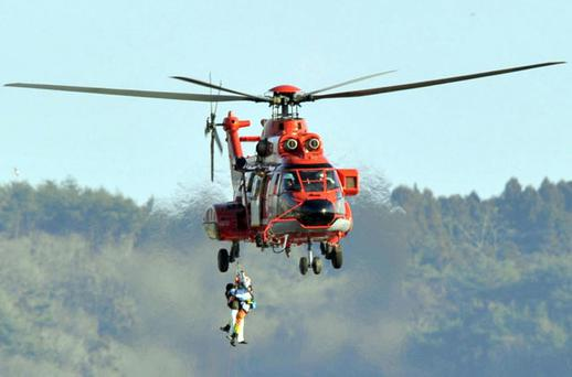 A person who's stranded in a building is plucked by a rescue helicopter. Photo: AP
