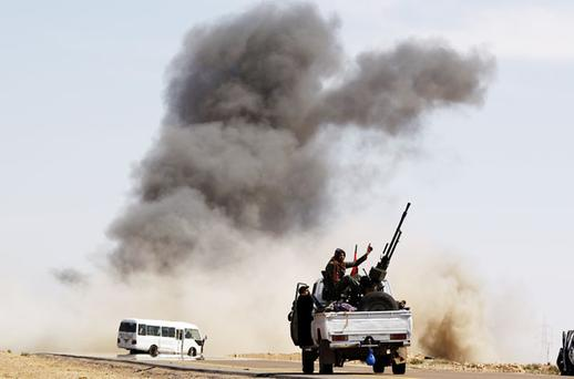 DESERT STORM: A rebel fighter gestures as he sits on a truck with an anti-aircraft gun during an air strike by Gaddafi forces at a checkpoint in Al Ugaila. Photo: Reuters