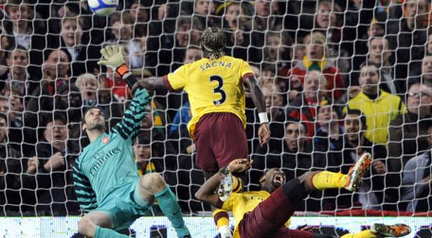 Arsenal goalkeeper Manuel Almunia makes a save while Bacary Sagna collides with Johan Djourou in the incident which saw the latter dislocate his shoulder. Photo: Reuters