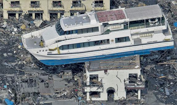 A ferry is stranded on a building in Otsuchi, Iwate Prefecture, northern Japan, yesterday,after Friday's catastrophic tsunami devastated the area