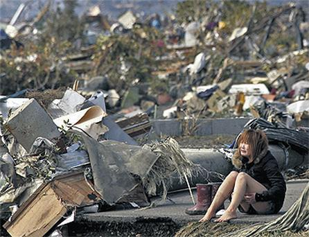 A woman cries amid the debris caused by the massive earthquake and the ensuing tsunami, in Natori, northern Japan