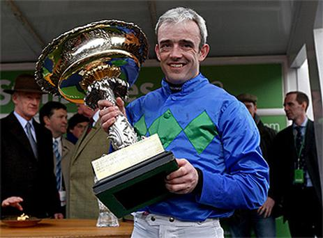 Ruby Walsh collects the trophy after his mount Hurricane Fly won yesterday's big race, the Champion Hurdle. Photo: PA
