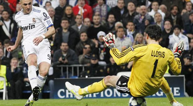 Real Madrid's Karim Benzema scores past Olympique Lyon's goalkeeper Hugo Lloris in their Champions League last 16 match last night. Photo: Reuters