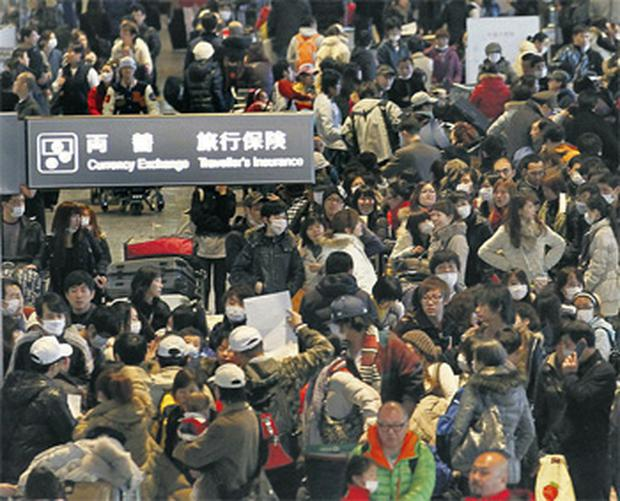 Crowds queue to check in for flights leaving Japan at Narita Airport yesterday