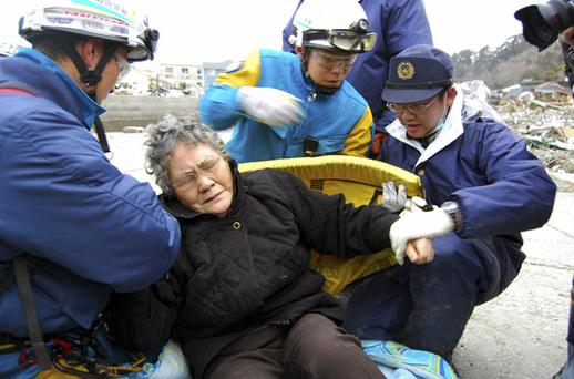 Rescue workers carry Sumi Abe away from the rubble in Ishinomaki, Japan, yesterday. Photo: REUTERS