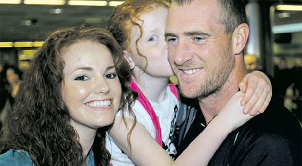 Star player John Mooney is welcomed home by his fiancee Helena Grant and their eight-year-old daughter Alisha at Dublin Airport yesterday