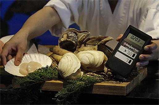 Imported seafood from Japan is screened for radiation by a chef at a Japanese restaurant in Hong Kong. Photo: AP