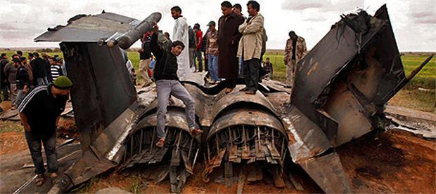 Locals swarm to the US Air Force F-15E fighter jet after it crashed near the eastern city of Benghazi, Libya, yesterday