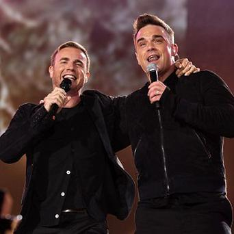 Robbie Williams says he and Gary Barlow are competing to get trim for the Take That tour