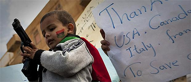 A gun was handed over to a boy during a rally in support of the allied air campaigns against Col Gaddafi in Benghazi, eastern Libya