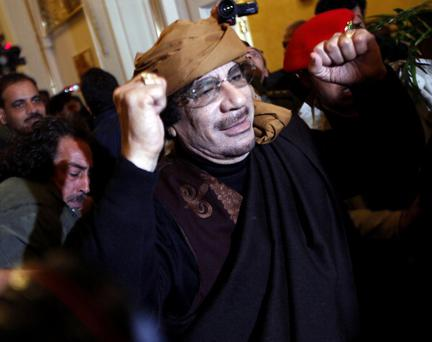 Libyan strongman Moamer Kadhafi gestures as he arrives at the Rixos hotel in the capital Tripoli on March 8, 2011. Earlier in the day Kadhafi warned of dire consequences for North Africa and Europe if there was any Western interference in his country's affairs, in a telephone conversation with the Greek Prime Minister George Papandreou. AFP PHOTO/MAHMUD TURKIA (Photo credit should read MAHMUD TURKIA/AFP/Getty Images)
