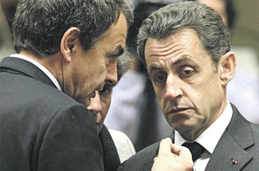 French President Nicolas Sarkozy, right, speaks with Spain's Prime Minister Jose Luis Rodriguez Zapatero at the EU summit in Brussels yesterday