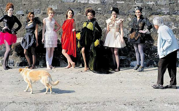 Vivienne Myles and her dog Cara walk by models on Sandymount Strand wearing designs shortlisted for the DIT Alfa Romeo Fashion Show yesterday.