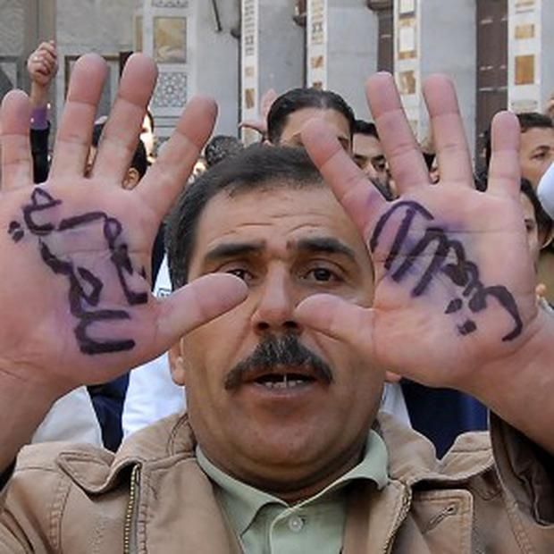 An anti-Syrian government protester displays Arabic words on his hands, reading 'Yes for freedom, no to violence' (AP)