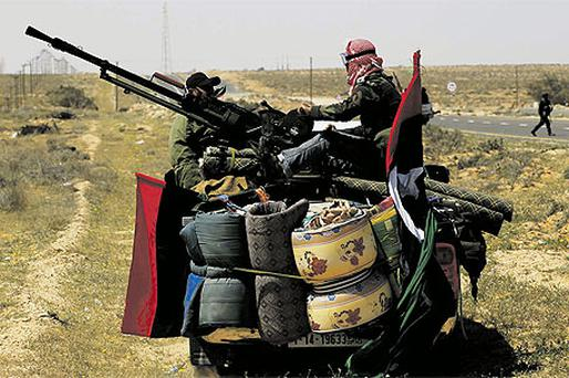 ebel fighters move across the desert in pursuit of forces loyal to Gaddafi some 120km east of Sirte in eastern Libya, yesterday