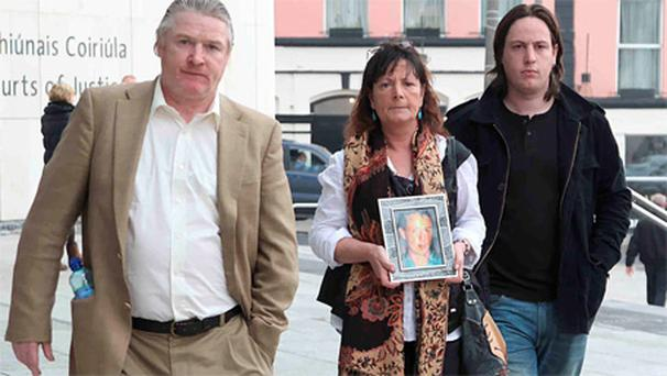 Daniel Fitzgerald's father Noel leaves court yesterday with his wife Teresa and son Ned. Teresa is carrying a picture of her son Daniel, who was murdered by Kenneth Collopy